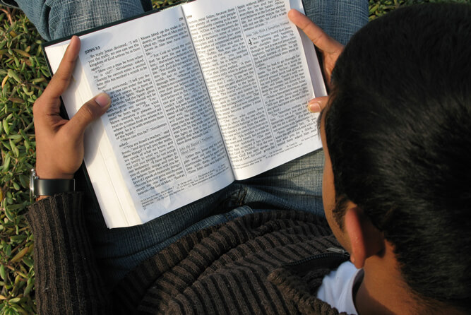A young boy reading the Bible outside