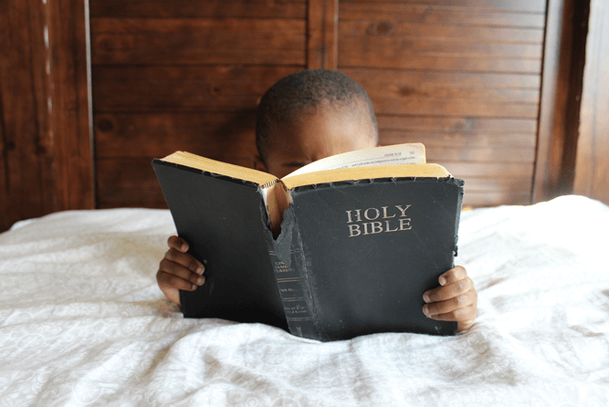 Little boy reading the Bible in the bed