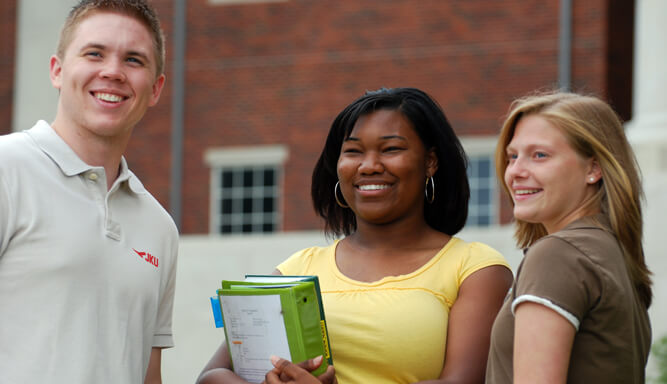 Three teens standing outside of school