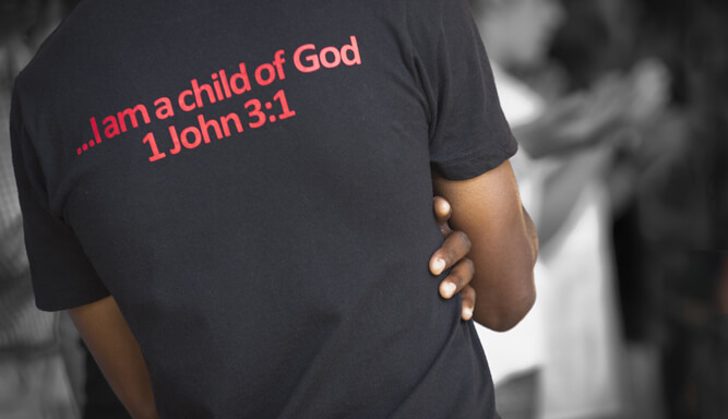 A black male with a religious shirt on.