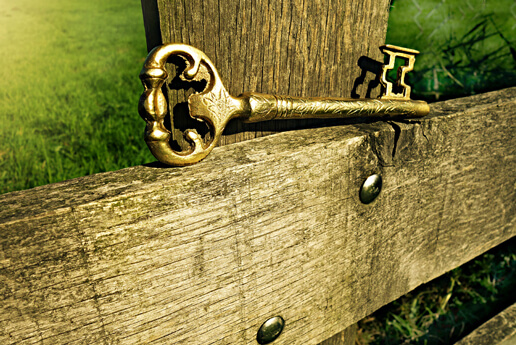 A gold key lying on a wooden fence