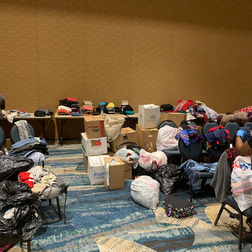 Boxes and bags of clothes and goods on tables