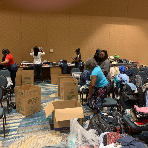Church member folding up clothes and filling boxes
