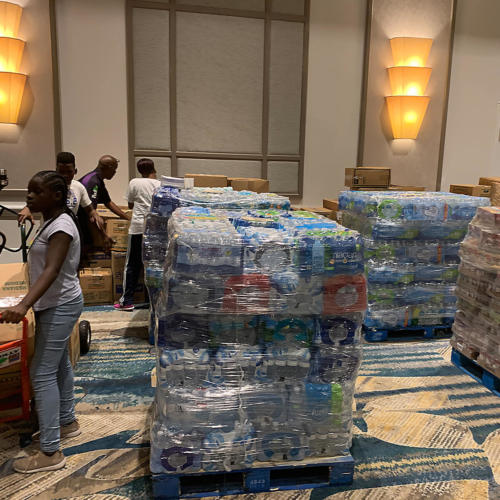 Cases of water on pallets next to church members